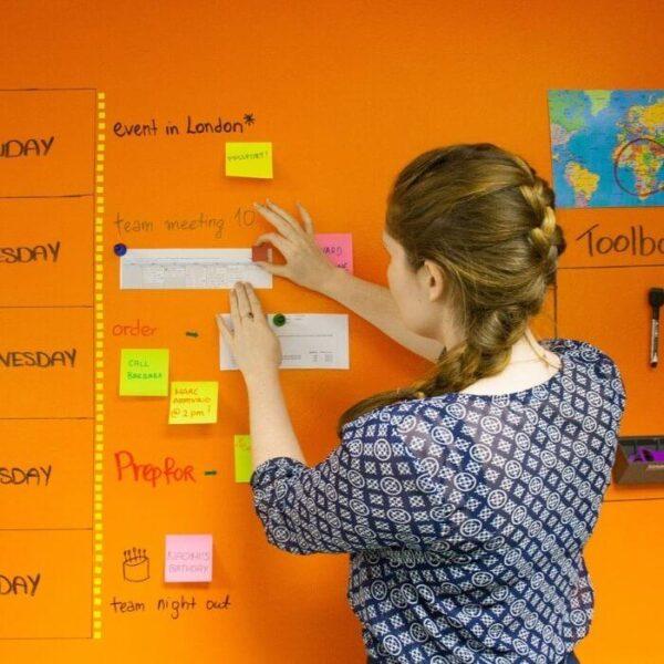 Ženska pritrjuje papir na magnetno steno prebarvano z magnetno piši briši barvo.