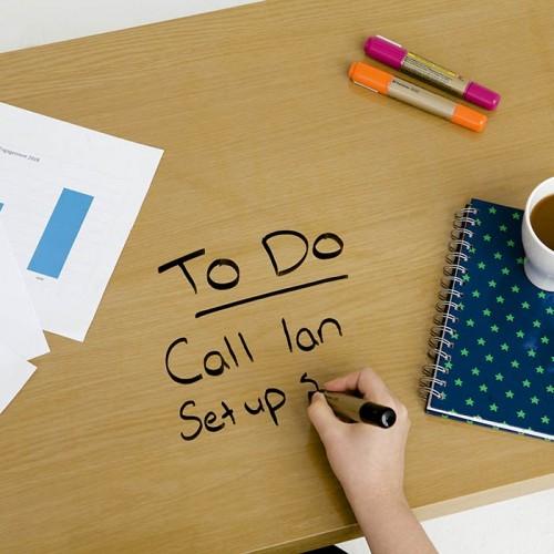 Seznam opravil napisan na transparentne samolepilno piši briši folijo nanešeno na pisalno mizo.