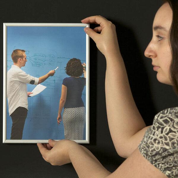 Ženska obeša okvir na steno s super, ki je pobarvana z magnetno barvo.