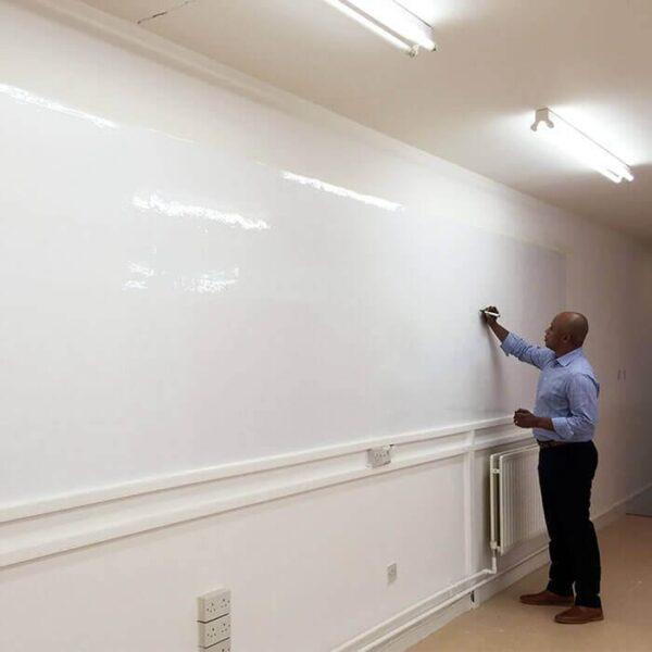 Človek piše na sijajni površini Smart piši briši tapeti.