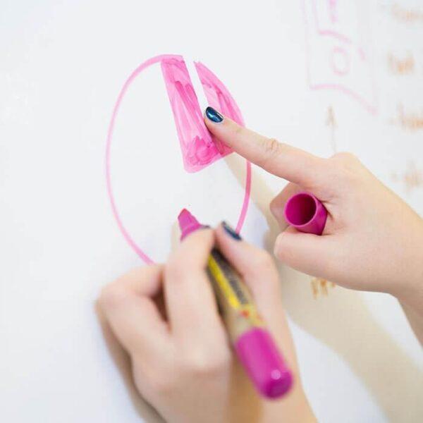 Človeška roka, ki riše z roza flomasterjem na Smart piši briši beli tapeti.