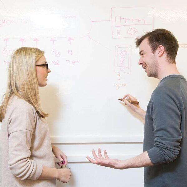 Med sestankom človek riše na Smart pisarniški piši briši površini v beli barvi.