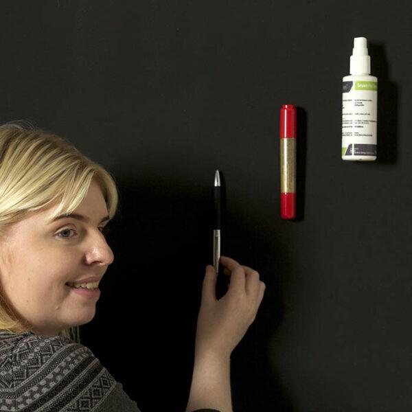 Ženska pritrjuje stvari na steni z magnetno barvo.